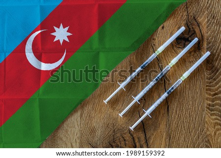 Concept of the ongoing efforts by Azerbaijan to deliver and distribute COVID-19 vaccines with three syringes on a wooden table ready to use with an Azeri Flag. Copy Space for Text and Graphics.