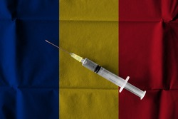 Concept of the ongoing efforts by Romania to deliver and distribute COVID-19 Vaccine with a syringe ready to use on a Romanian flag.