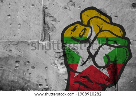 Concept of the public unrest and demonstrations in Myanmar after the Military Coup. Painted Fist on a concrete Wall colored in the Myanmar Flag. 3D Illustration. 3D rendering Photo stock ©