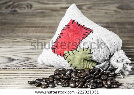 Concept of the thrift storing - Coffee beans in the burlap sack with the patch on a wooden background