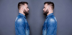 Concept of the twins. Two twin brothers in jeans shirts look at each other against a gray background.