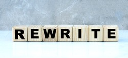 concept of the word REWRITE on cubes on a gray background. Business concept.