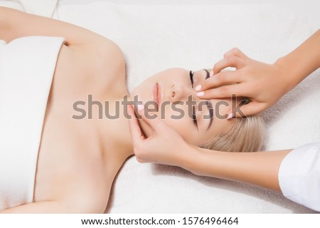 Concept of therapeutic anti-aging skin tightening facial treatments. Close-up hands of an unidentified young woman masseur doing facial massage to beautiful young caucasian client woman at spa salon. Photo stock ©