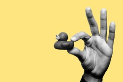 Concept of think different, be original, think outside the box, the childhood. Hand holding a black plastic duck with two fingers. Black and white image with yellow background