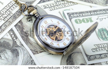 Concept of time is money, old watch on a pile dollar notes