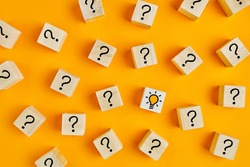 Concept of to find a creative idea or problem solving. Question mark and light bulb icons on wooden cubes on yellow background.