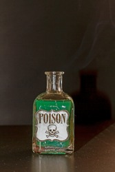 Concept of toxic thing. Transparent bottle with green liquid simulating poison. The label reads poison along with a skull and two tibias