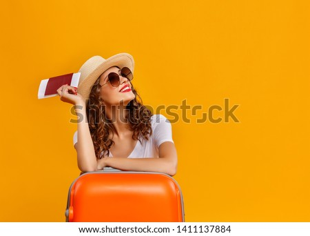 concept of travel. happy woman girl with suitcase and passport on  yellow colored background