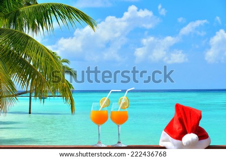 Concept of tropical christmas vacations -- Two tropical fresh juices and red santa hat near the beautiful tropical beach with palm trees