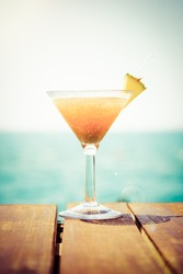 Concept of tropical vacation. Exotic cocktail on the pier. Luxury holiday background. Orange cocktail with sea view. Vertical, warm toned