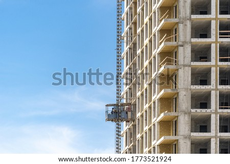 Concept of unfinished skyscraper. Perfect geometric building under construction with rockwool insulation on exterior and scaffolding equipment against blue sky on copy space background