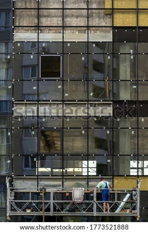 Concept of unfinished skyscraper. Vertical photo of building under construction with large glass windows and professional worker man in special scaffolding equipment