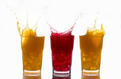 Concept of unique and one of a kind represented with splashes on glasses of orange juice and strawberry juice