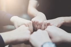Concept of unity and work together, close-up, young business people putting hands to each other, soft focus