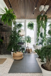 Concept of urban jungle interior. Vertical shot of cozy fully furnished bathroom decorated with green plants and natural organic design elements, white bathtub near panoramic window on pebble floor