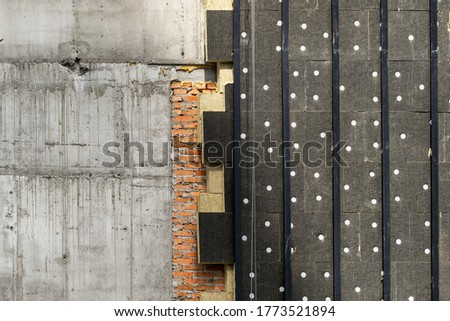 Concept of urban structure. Close up element of building under construction with rock wool insulation on exterior and copy space on concrete wall