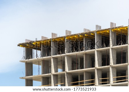 Concept of urban structure. Element of new modern building under construction with reinforcement formwork in city, against blue copy space sky on background