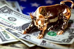 Concept of US money and trading. Us dollar bills and american flag under copper bull. Macro image.