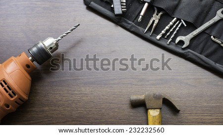 Concept of used power drill machine, hammer and some mechanic or carpentry tools kit on wooden board with room for text