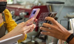 Concept of using smartphones to scan QR codes to make payments or earn points in restaurants. Using technology in the food business
