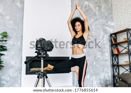 Concept of video of training, yoga video tutorial. A young African-American woman practices yoga and records herself on camera. Online trainer, coach