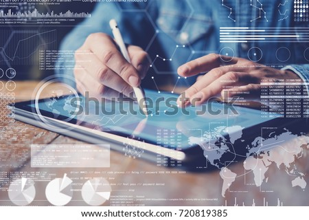 Concept of virtual diagram,graph interfaces,digital display,connections icon.Male hand holding stylus pencil on display of contemporary electronic tablet.Blurred background. Horizontal