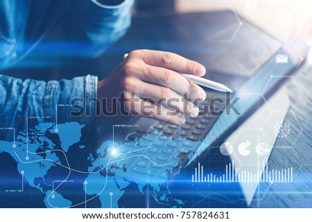 Concept of virtual diagram,graph interfaces,digital display,connections,statistics icons.Man using stylus pencil on digital display of contemporary electronic tablet.Blurred background. Horizontal