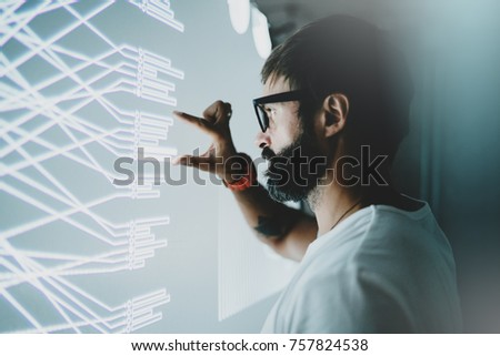 Concept of virtual panel display,diagram,digital graph interfaces.Attractive coworker touching virtual panel with graphs.Blurred background. Horizontal #757824538