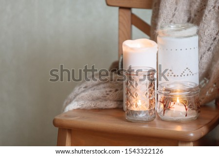 Concept of warming canlelight, winter autumn weekend holiday relax time, copy space, monochrome, cozy atmosphere, cozy home interior details, toned photo #1543322126