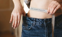Concept of weight loss. Girl holds jeans in her hand and shows a thin waist and measures her waist with a centimeter . Thin woman body in big jeans.   Diet concept