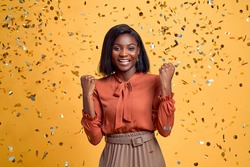 Concept of winning popular being the best one. Beautiful charming lovely lucky woman raising arms up isolated on yellow background.