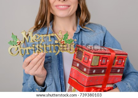 Concept of winter holidays. Happy smiling teenage girl holding big gift box and christmas decoration. Cropped photo, isolated on gery background