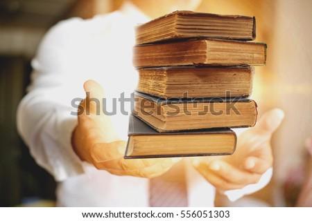 Concept of wisdom, book in man's hands in gesture of giving. #556051303