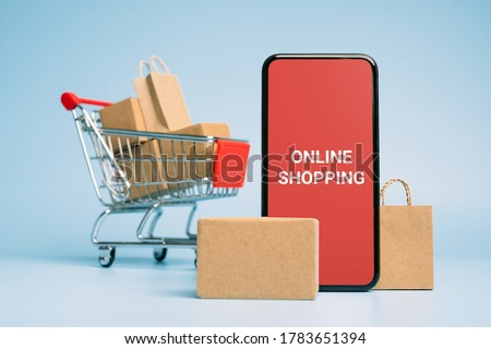 Concept online Sopping. boxes and shopping bag on Trolley with Smartphone Online Shopping screen.