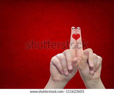 Concept or conceptual human or female hands with two fingers painted with a red heart over a old vintage paper background for valentine romantic love couple young family or wedding