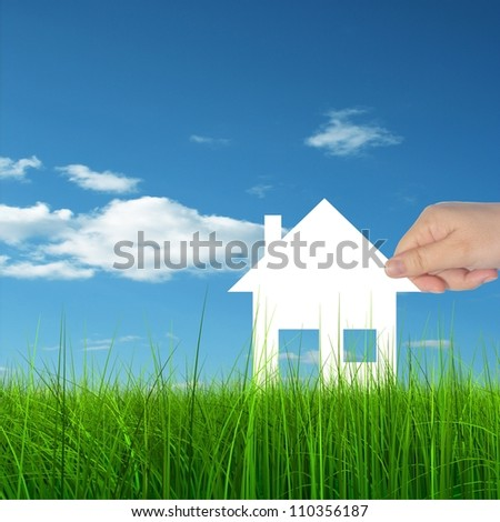 Concept or conceptual White paper house held in hand by a man in a green summer grass over a blue sky background with clouds, as a symbol for construction,eco,ecology,loan,mortgage ,property or home