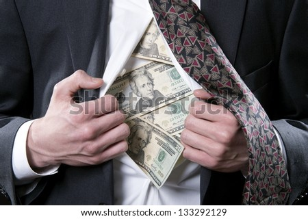 Concept photo for hidden money showing a businessman pulling back his shirt and tie exposing twenty dollar bills