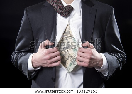 Concept photo for hidden money showing a businessman pulling back his shirt exposing twenty dollar bills