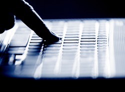Concept photo in high contrast black and white of hacker's single finger on keyboard