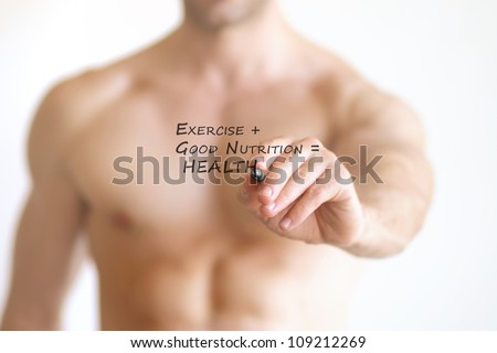 """Concept photo of a fit young shirtless man writing the formula for good health on transparent board that reads """"Exercise + Good Nutrition = Health"""""""
