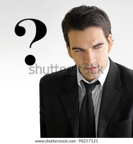 Concept photo of a good looking young businessman in elegant black and white suit with question mark against white background