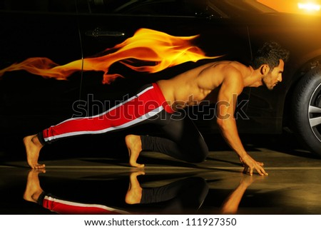 Concept photo of a young muscular athlete posed ready to run with car and flame behind him