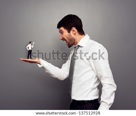 concept photo of big boss screaming at the small man with megaphone