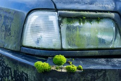 Concept photo of extremely abandoned decaying car with green moss growing on metal surface.