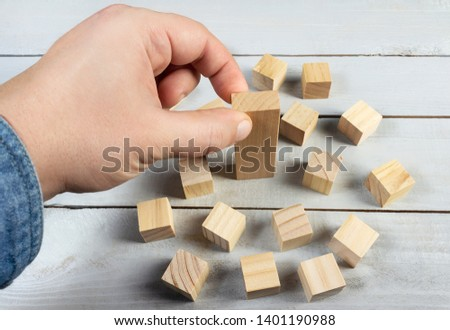 Concept photo of hand in jeans shirt putting a bigger wooden block in surrounding of a smaller ones on a table surface background. #1401190988
