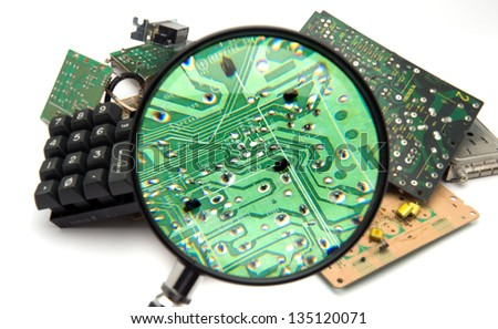Concept photo showing digital computer parts discarded in garbage pile examined with magnifying glass