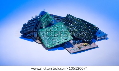 Concept photo showing digital computer parts discarded in garbage pile with blue light