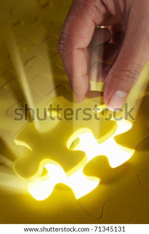 Concept photo using piece of puzzle with ray of light comes out from missing piece