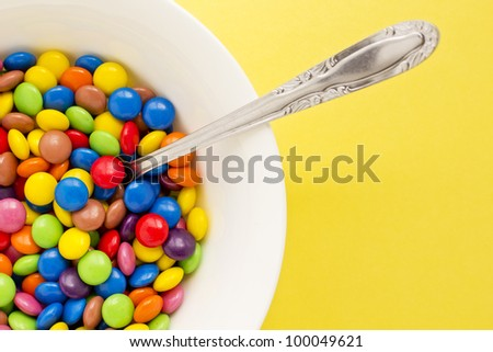 Concept photograph of a bowl full of colored chocolate buttons representing unhealthy diet.