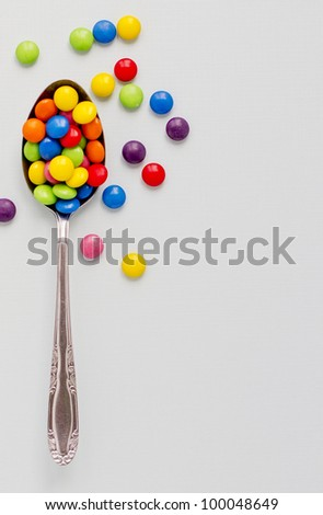 Concept photograph of a spoon full of colored chocolate buttons representing unhealthy diet.